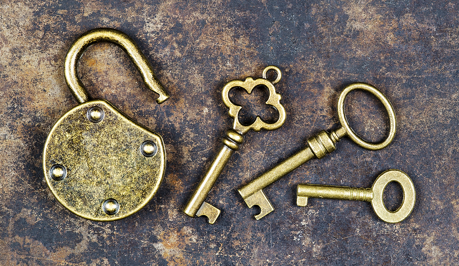Viintage golden keys and unlocked padlock on a rusty metal background, escape game room concept